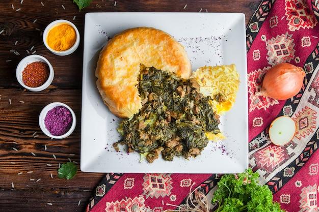 Vista dall'alto pilaf in una pita con erbe, cipolle e spezie. piatto orientale tradizionale su una superficie di legno scuro orizzontale