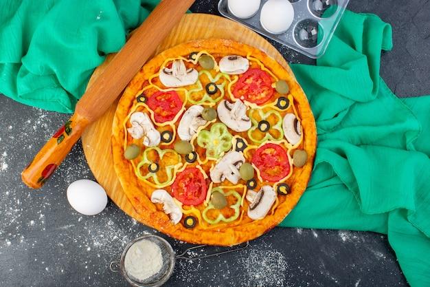 Vista dall'alto pizza ai funghi con pomodori olive funghi tutti affettati all'interno con farina sulla scrivania grigia pasta per pizza tessuto verde cibo italiano