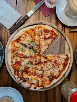 Vista dall'alto-pizza vegetale su un tavolo di legno rustico.