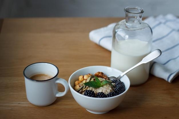 Vista dall'alto porridge di farina d'avena, caffè, bacche, noci e una bottiglia di latte su un tavolo di legno
