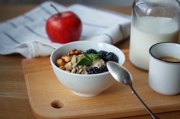 Vista dall'alto porridge di farina d'avena, caffè, mela, bacche, noci e una bottiglia di latte su un tavolo di legno