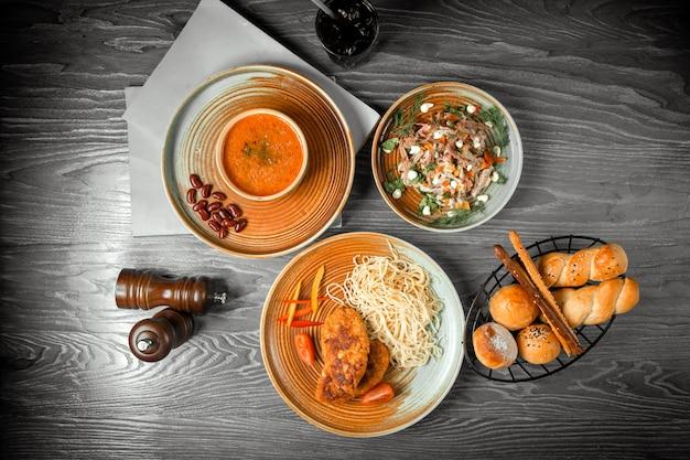 Vista dall'alto primo e secondo piatto di insalata di zuppa di lenticchie e cotolette con pasta e una bibita sul tavolo
