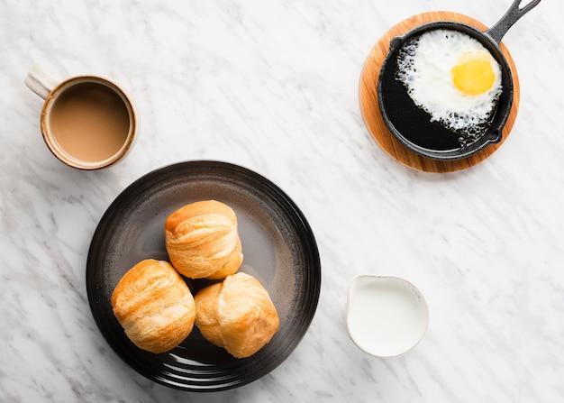 Vista dall'alto raccolta di uova per la colazione in padella accanto al pane