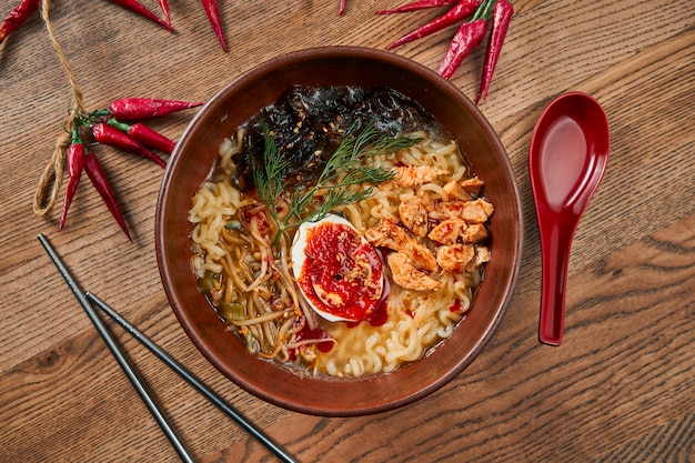 Vista dall'alto ramen - tagliatelle servite con brodo, salsa di soia o miso e condimenti come fette di maiale, uova e nori in una ciotola di ceramica su legno.