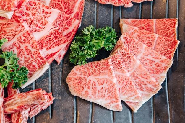 Vista dall'alto ravvicinata di premium rare slices molte parti di manzo wagyu a5 con trama marmorizzata sul piatto di pietra servito per yakiniku