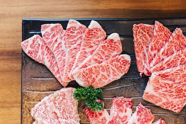 Vista dall'alto ravvicinata di premium rare slices molte parti di manzo wagyu a5 con trama marmorizzata.