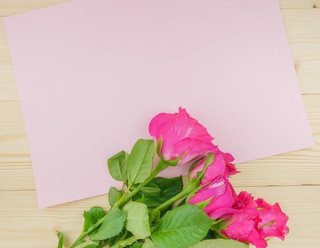 Vista dall'alto rose rosa su fondo in legno beige con copia spazio