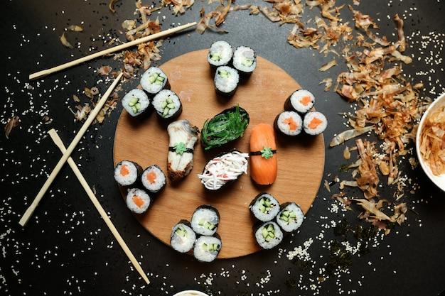 Vista dall'alto rotoli di kappa maki con shake maki e sashimi sushi con le bacchette su un supporto