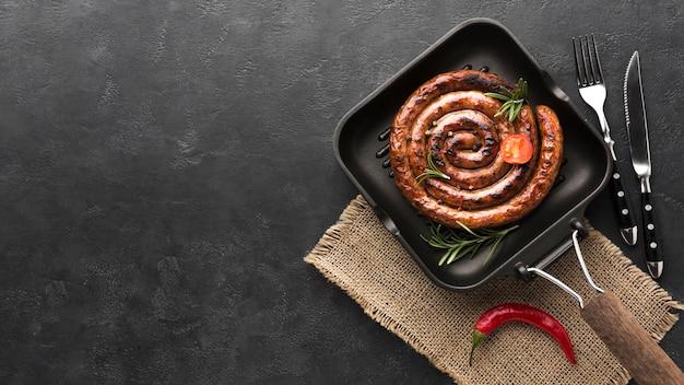 Vista dall'alto salsiccia alla griglia in una padella sul tavolo