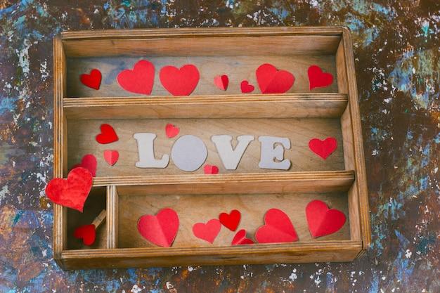 Vista dall'alto scatola di legno con cuori di carta e la parola amore
