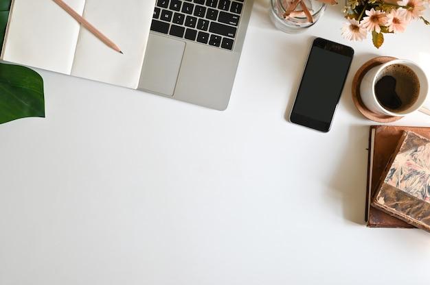 Vista dall'alto scrivania con computer, telefono cellulare caffè e forniture per ufficio sul tavolo e le finestre del mattino si accendono.