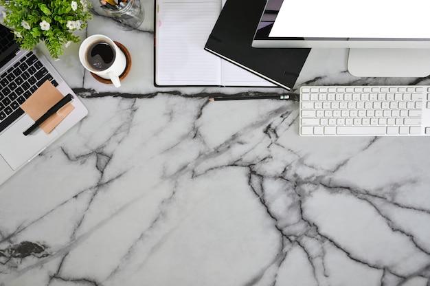 Vista dall'alto scrivania scrivania computer, caffè, carta nota e penna con pianta sul tavolo di marmo.