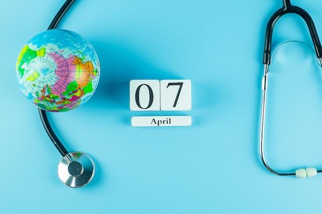 Vista dall'alto stetoscopio globe e calendario del 7 aprile. giornata mondiale della salute