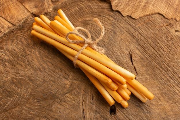 Vista dall'alto stick cracker legati con una corda sottile sulla scrivania in legno cracker croccante snack salato foto
