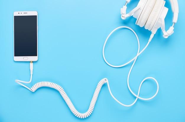 Vista dall'alto su gadget su sfondo blu, composizione di cuffie bianche e telefono