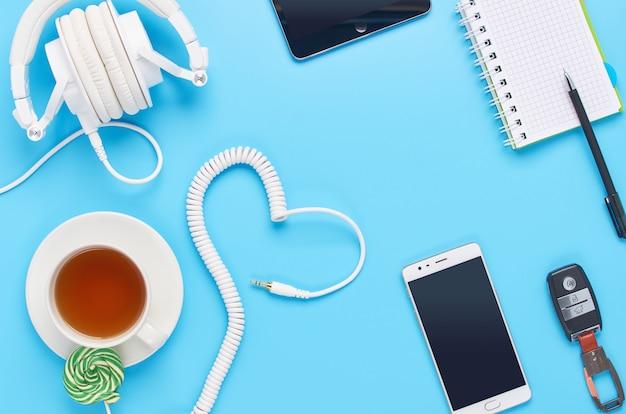 Vista dall'alto su gadget su sfondo blu, composizione di cuffie bianche, telefono, tablet, vetro con un drink e chiavi della macchina