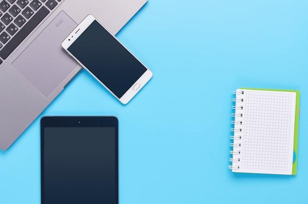 Vista dall'alto su gadget su sfondo blu, la composizione di un computer portatile, cuffie bianche, telefono, vetro con un drink e chiavi della macchina