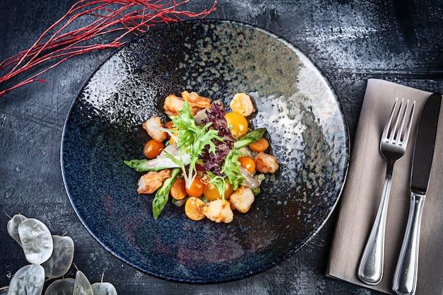 Vista dall'alto su insalata calda con insalata di gamberi, pomodorini e asparagi servita in una ciotola scura su sfondo scuro. cibo piatto. chiuda sulla vista su pranzo con lo spazio della copia per il disegno. frutti di mare