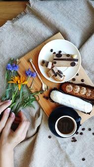 Vista dall'alto su mani femminili con fiori estivi vicino a una tazza di caffè nero e servito eclairs