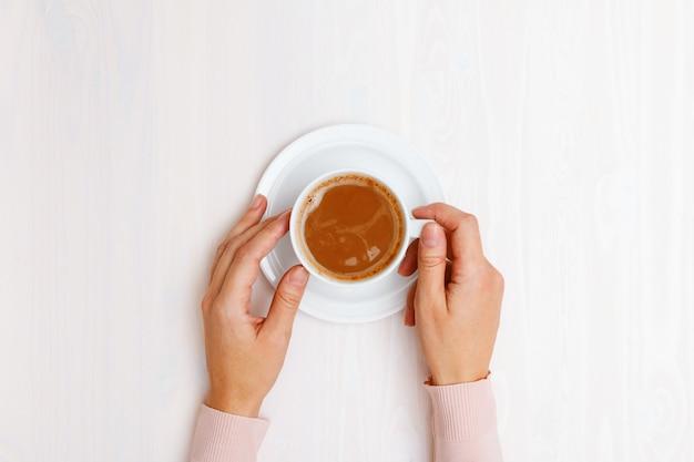 Vista dall'alto su mani femminili in possesso di una tazza di caffè con latte al tavolo.