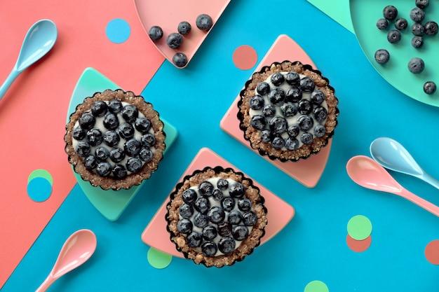 Vista dall'alto su mini torte di crema pasticcera ai mirtilli per la festa di compleanno per bambini