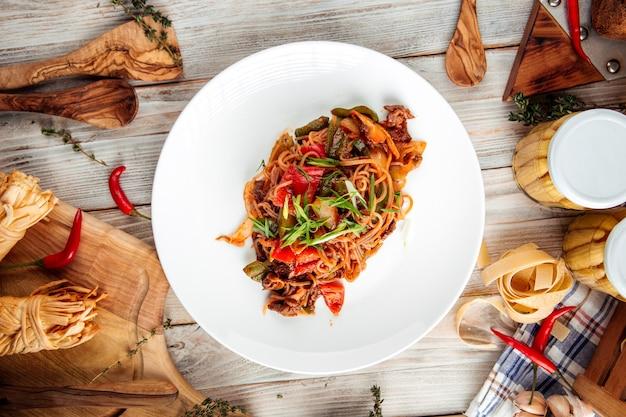 Vista dall'alto su spaghetti asiatici con carne di manzo e verdure nel piatto bianco