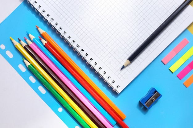 Vista dall'alto su un quaderni, matite, temperino su sfondo blu. torna al concetto di scuola