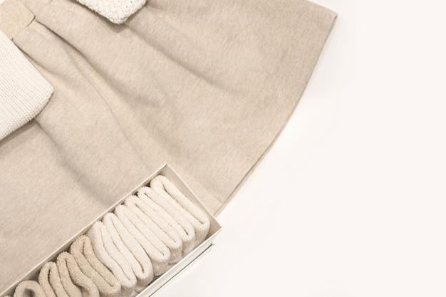 Vista dall'alto su una gonna beige, maglioni e calze fatte di tessuti naturali che giacciono sul tavolo