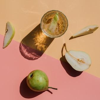 Vista dall'alto succo di pera circondato da fettine di pera