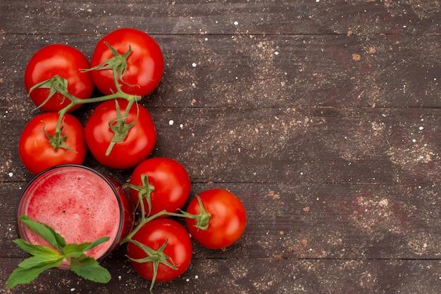 Vista dall'alto succo di pomodoro fresco con foglia e interi pomodori rossi freschi su marrone
