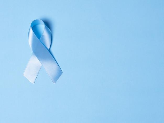 Vista dall'alto sul nastro di raso blu simbolo della consapevolezza del cancro alla prostata su uno sfondo blu brillante. concetto di medicina e assistenza sanitaria