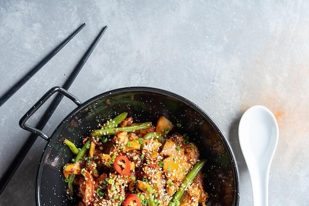 Vista dall'alto sul pad thai, o phad thai in padella di pasta di riso con verdure e pollo, peperoncino piccante e prezzemolo in ciotola nera sulla superficie di pietra grigia