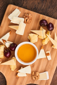 Vista dall'alto sul set di formaggio parmigiano, mozzarella, camembert e una tazza di olio d'oliva su una tavola di legno