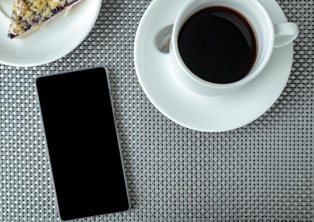 Vista dall'alto sul tavolo con torta di smartphone, caffè nero e mirtillo