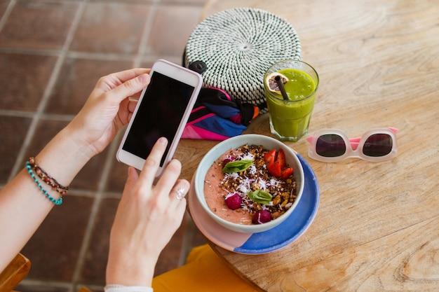 Vista dall'alto sulla bella donna in pantaloni gialli utilizzando il telefono e godendo gustoso cibo vegan