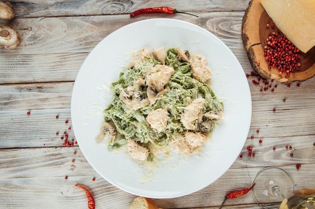 Vista dall'alto sulla pasta verde fettuccine alfredo con funghi e pollo sul tavolo di legno
