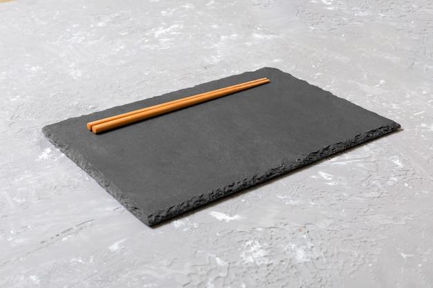 Vista dall'alto sulla piastra di ardesia nera con le bacchette di legno su sfondo scuro, copia spazio