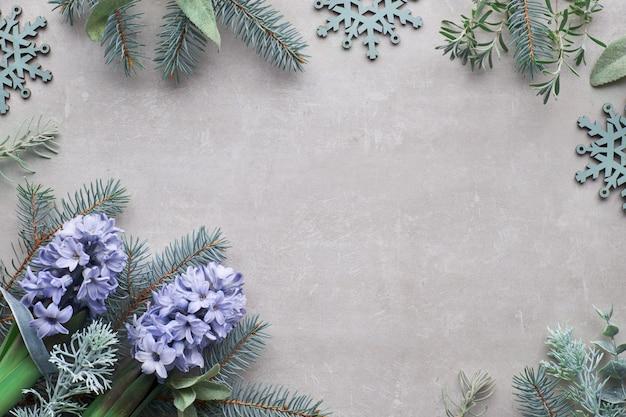 Vista dall'alto sulla superficie del calcestruzzo invernale con ramoscelli di abete e fiori di giacinto blu,
