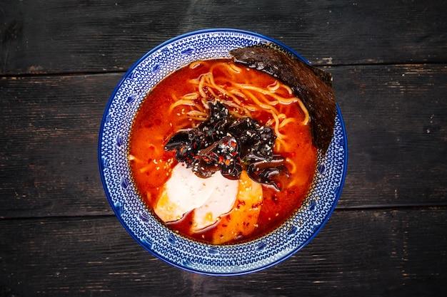 Vista dall'alto sulla zuppa di spaghetti ramen piccante giapponese miso cile con petto di pollo