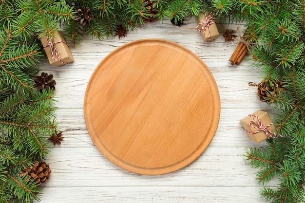 Vista dall'alto, svuotare la piastra rotonda di legno sullo sfondo di natale
