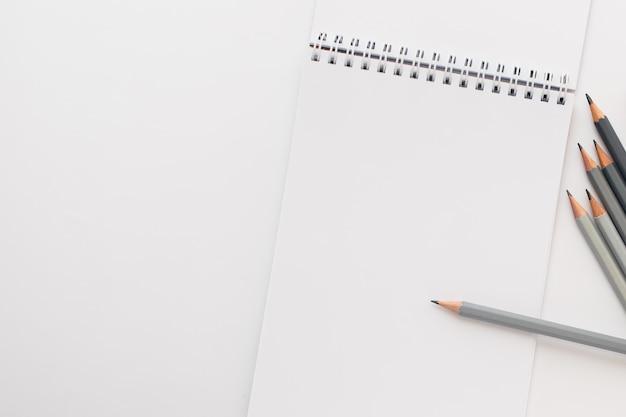 Vista dall'alto, taccuino vuoto con matite su bianco.