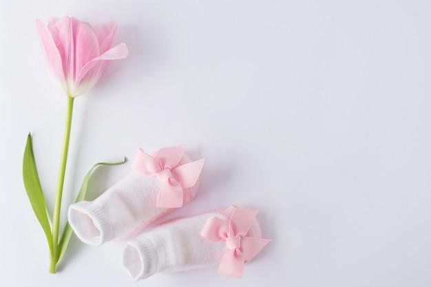 Vista dall'alto tavolo stivaletti per bambini e fiore per sviluppare il concetto