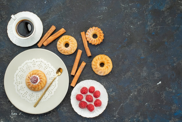 Vista dall'alto tazza di caffè con biscotti torta cannella e lamponi freschi sulla superficie scura