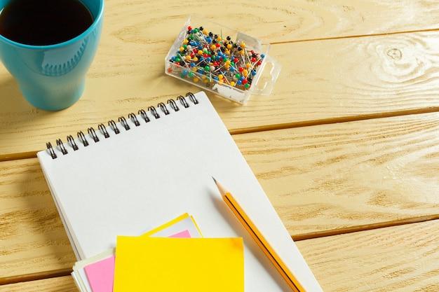 Vista dall'alto, tazza di caffè con caffè, penna che mette sul taccuino in bianco,