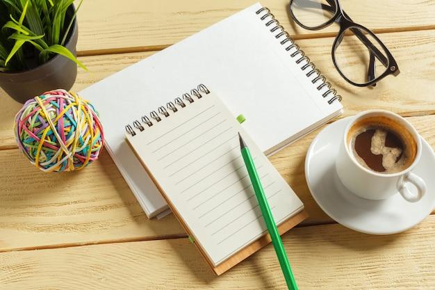 Vista dall'alto. tazza di caffè con caffè. penna che mette sul taccuino in bianco.