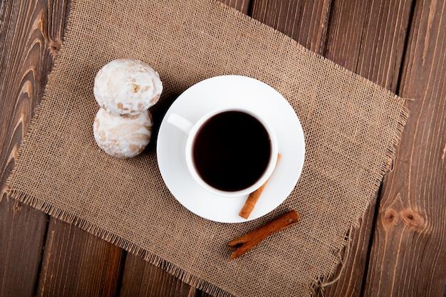 Vista dall'alto tazza di caffè con cannella e pan di zenzero sul tavolo di legno