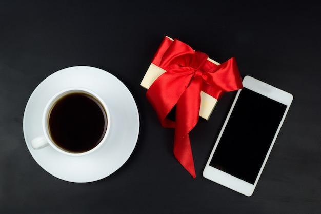 Vista dall'alto tazza di caffè, confezione regalo e telefono cellulare