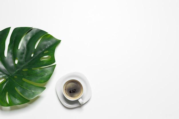 Vista dall'alto tazza di caffè e foglia di monstera