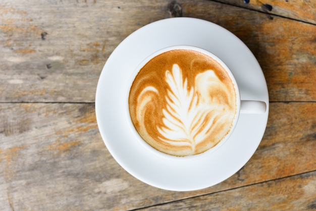 Vista dall'alto, tazza di caffè latte art sul vecchio tavolo in legno vintage con copia spazio per il testo