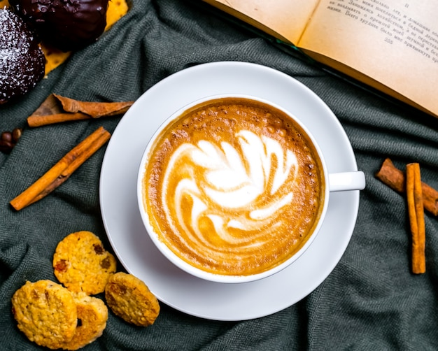 Vista dall'alto tazza di cappuccino con biscotti e un libro sul tavolo